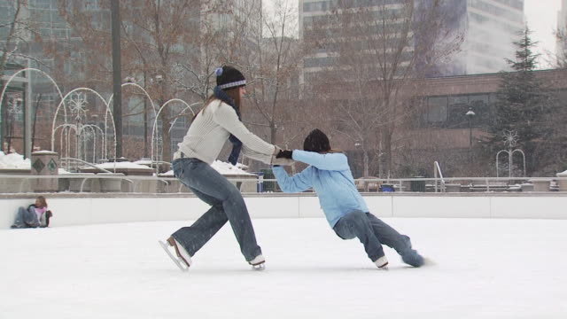 a woman playing with a young girl at a busy ice rink - altri spezzoni di questa ripresa 1145 video stock e b–roll
