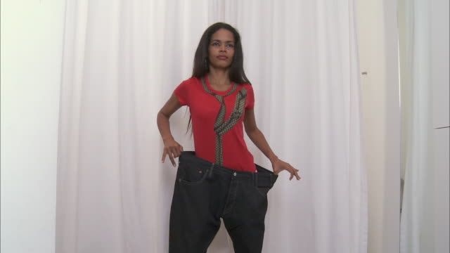 ms woman playing with baggy pants in clothes store / brussels, belgium - pants stock videos and b-roll footage