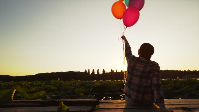 woman playing with balloons by the lake. - ethereal stock videos and b-roll footage