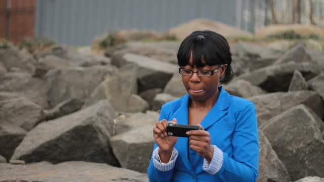 woman playing with cell phone on rocks