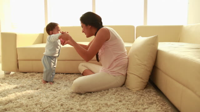 woman playing with her baby  - primi passi video stock e b–roll