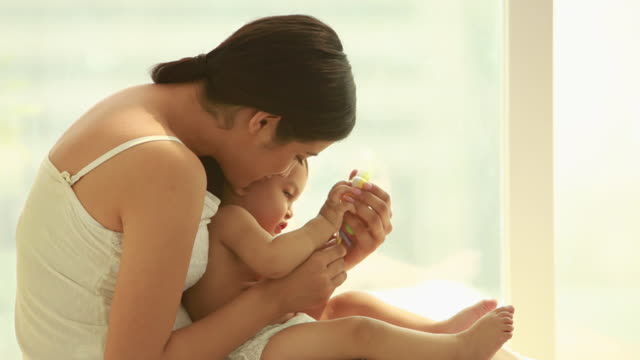 vídeos de stock e filmes b-roll de woman playing with her baby  - colo