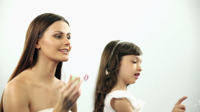 Woman playing with her daughter with a bubble wand