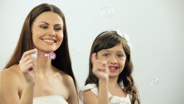 woman playing with her daughter with a bubble wand  - hair accessory stock videos and b-roll footage