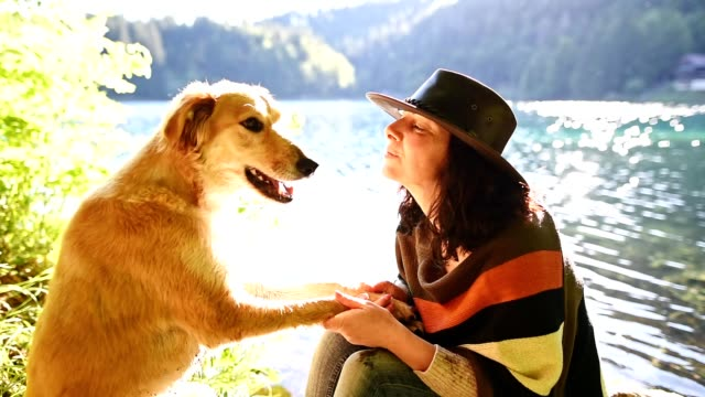 woman playing with her dog at the lake