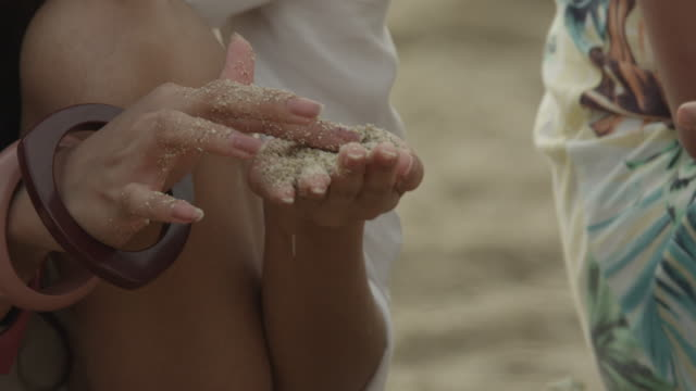 A woman playing with sand in her hands.