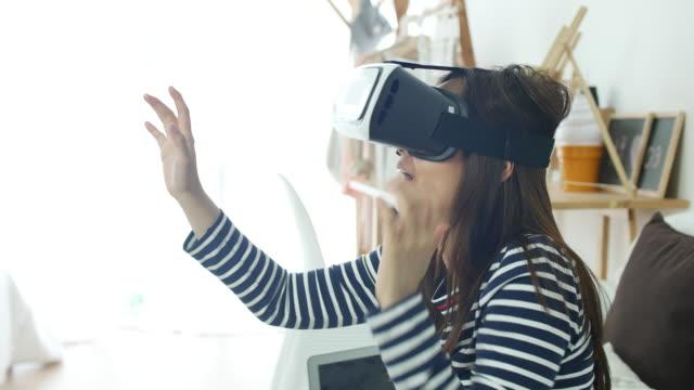 vidéos et rushes de femme jouant avec le casque de réalité virtuelle à la maison, vr lunettes - série d'émotions