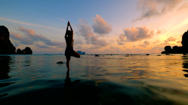 Woman playing Yoga at the beach in sunset sky