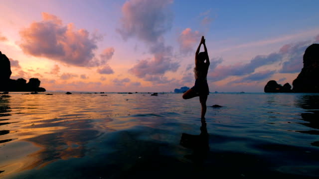 woman playing yoga at the beach in sunset sky - thailand stock videos & royalty-free footage