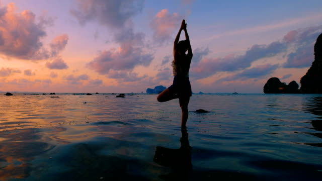 woman playing yoga at the beach in sunset sky - tranquility stock videos & royalty-free footage