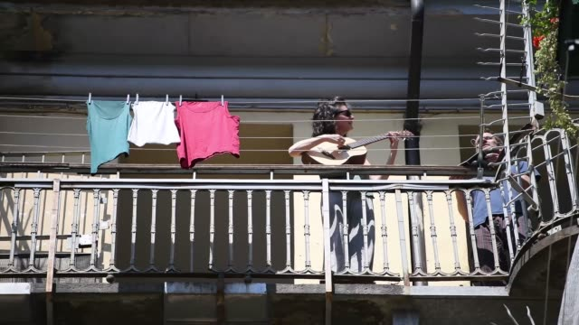 """stockvideo's en b-roll-footage met woman plays a guitar on the balcony during the flashmob during liberation day celebrations on april 25, 2020 in turin, italy. flashmob """"bella ciao""""... - balkon"""