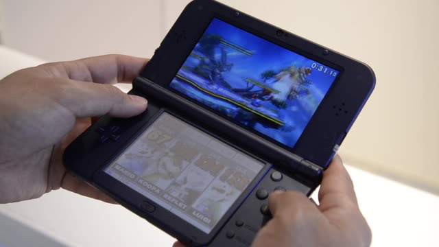 a woman plays a nintendo co 3ds ll handheld game console at the companys showroom in tokyo japan on thursday feb 5 a man plays a video game on a... - handheld video game stock videos & royalty-free footage