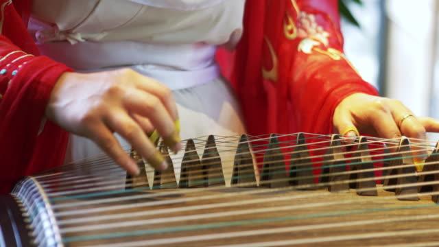 vídeos de stock, filmes e b-roll de mulher toca um instrumento tradicional chinês, o belo e melódico gu zhen - cultura chinesa