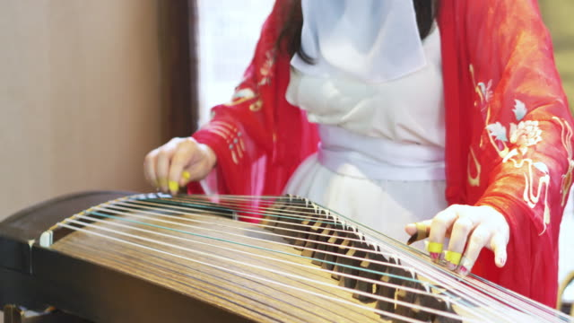 woman plays a traditional chinese instrument, the beautiful and melodic gu zhen - performer stock videos & royalty-free footage