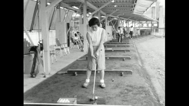 zo woman plays golf at a driving range in japan; 1966 - golf shoe stock videos & royalty-free footage