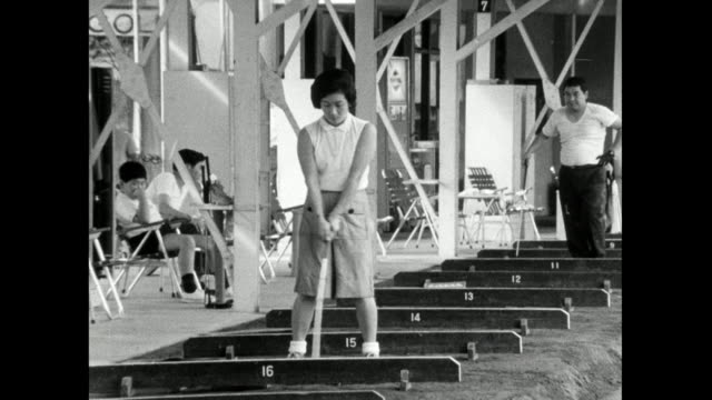 ws woman plays golf at a driving range in japan; 1966 - golf swing stock videos & royalty-free footage