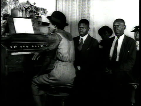 1939 ms woman plays organ as congregation stands at a church / usa - パイプオルガン点の映像素材/bロール