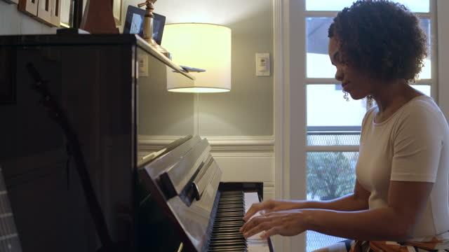 vídeos de stock e filmes b-roll de a woman plays piano for a friend, who listens via video conference. - tecla de piano