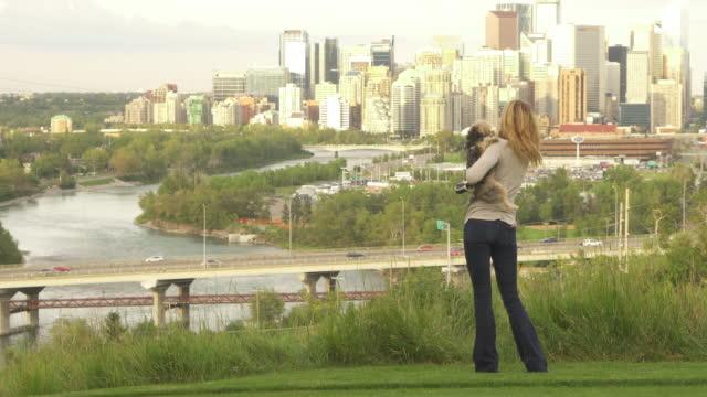 vídeos de stock e filmes b-roll de woman plays with dog in urban park, city skyline behind - trela de animal de estimação