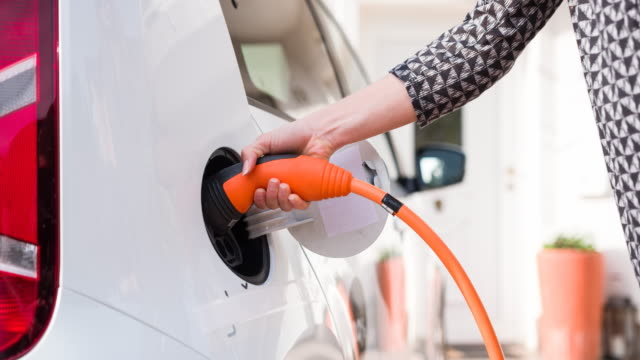 Woman plugging electric car in driveway to household charging system to recharge batteries