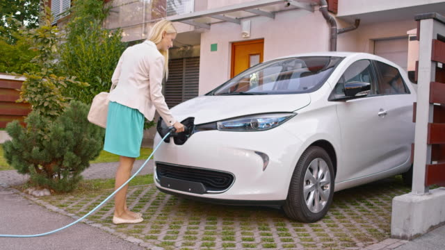 DS Woman plugging in electric car at home