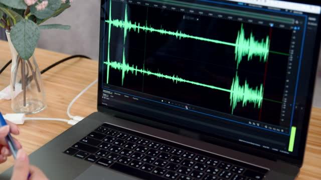 女性ポッドキャスト音声録音と編集の音波のデザインをラップトップ上 - マイク点の映像素材/bロール