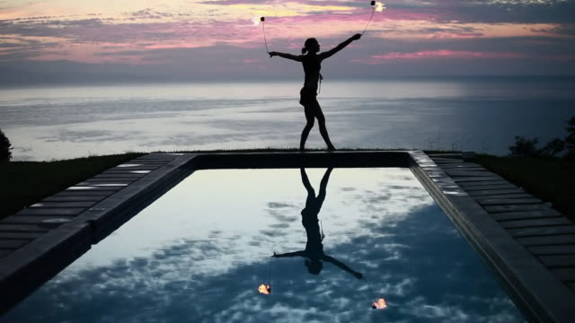ws woman poi dancer performing in front of pool with reflection of his silhouette in pool at sunrise / montezuma, costa rica - kelly mason videos stock videos & royalty-free footage