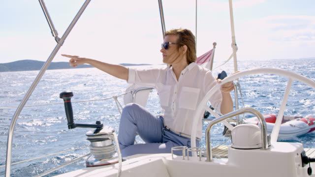 vidéos et rushes de femme de ws pointant quelque part alors que vous naviguez d'un voilier - capitaine de bateau