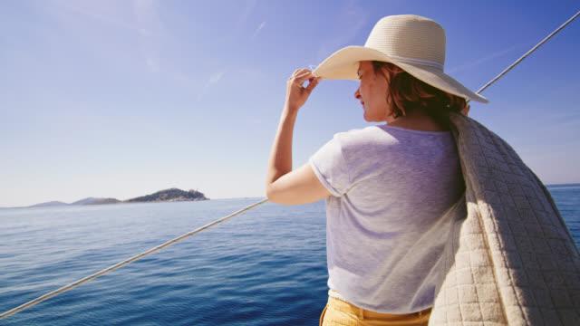 stockvideo's en b-roll-footage met ms-woman wijzend op het eiland tijdens het zeilen - zonnehoed hoed