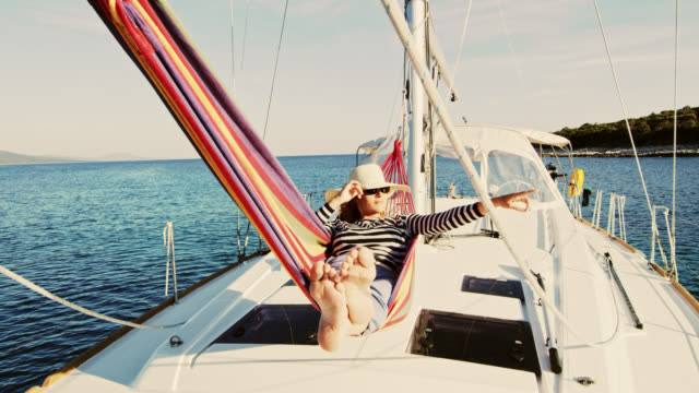 WS Woman pointing with finger at something while relaxing on a sailboat