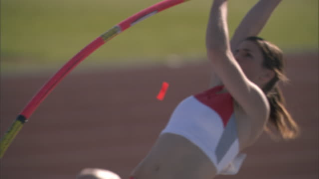 ws pan woman pole vaulting over pole / sheffield, england, uk - pole stock videos & royalty-free footage