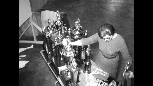 woman polishes collection of large trophies - trophy prize display of winning events - skåp med glasdörrar bildbanksvideor och videomaterial från bakom kulisserna