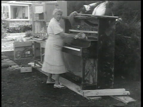 woman polishing piano / men removing large piece debris / men removing debris from car - rubble stock-videos und b-roll-filmmaterial