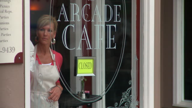 ms woman polishing window of cafe, changing closed sign / richmond, virginia, usa - closed sign stock videos and b-roll footage