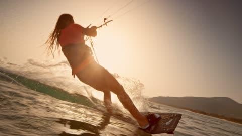 vídeos y material grabado en eventos de stock de slo mo mujer haciendo estallar en el aire en su kiteboard al atardecer - deporte de riesgo
