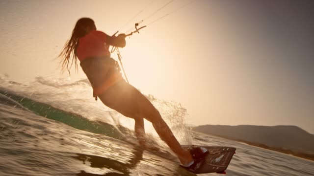 slo mo woman popping into the air on her kiteboard at sunset - tracking shot stock videos & royalty-free footage