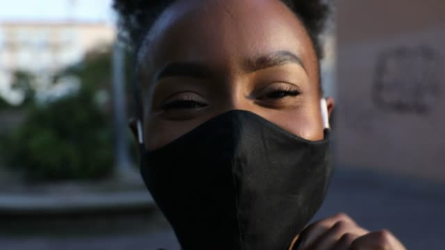vídeos de stock e filmes b-roll de woman portrait wearing a black cloth face mask - afro