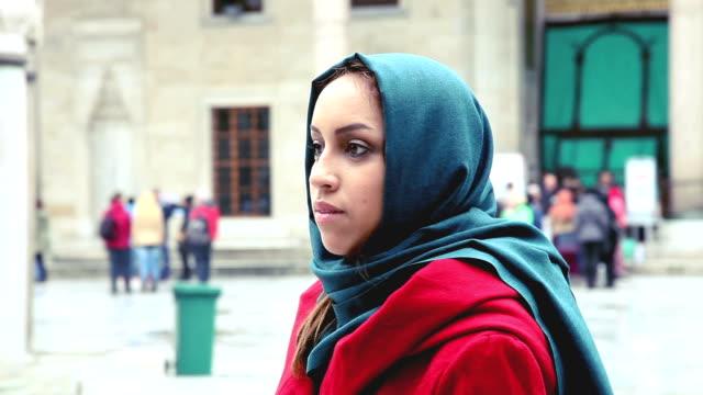 Retrato de una mujer usando un pañuelo de cabeza delante de mezquita