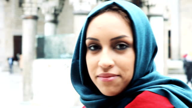 woman portrait wearing an headscarf in front of a mosque - headscarf stock videos & royalty-free footage