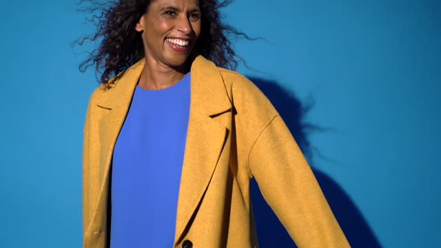 a woman poses against a blue background - tilt down stock videos & royalty-free footage
