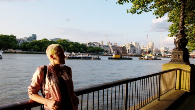 woman poses along the thames river in london, england during sunset. - naga river stock videos and b-roll footage