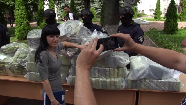 A woman poses for a photo next to bags of cocaine seized during a special operation after a pess conference of the leadership of the National Police...