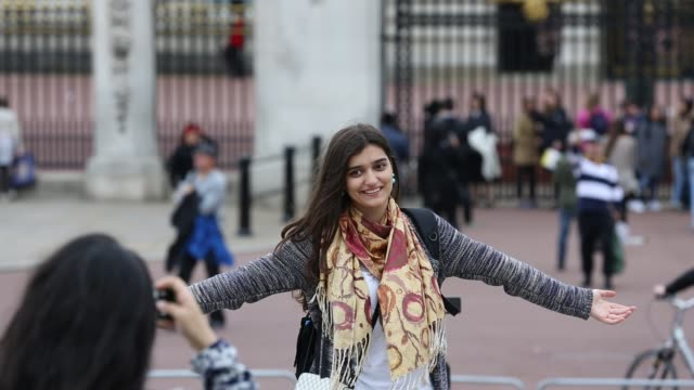 a woman poses for a photo outside buckingham palace, london, uk. - palace stock videos & royalty-free footage