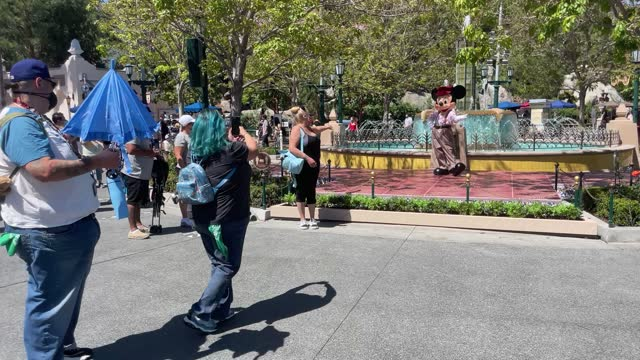 woman poses near a person dressed as disney character mickey mouse as disneyland and disney's california adventure reopen with social distancing and... - adventure stock videos & royalty-free footage