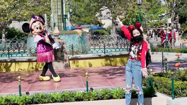 woman poses near a person dressed as disney character minnie mouse as disneyland and disney's california adventure reopen with social distancing and... - anaheim california stock videos & royalty-free footage