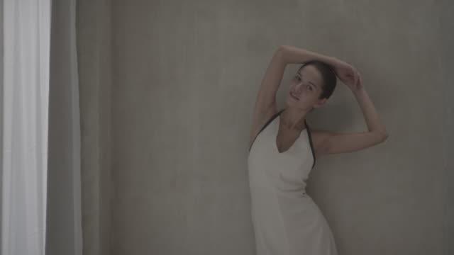 Woman posing against wall near window.