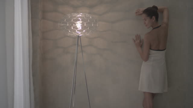 Woman posing against wall next to floor lamp near window.