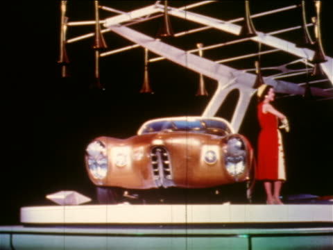 "1956 woman posing by gold oldsmobile ""car of the future"" on spinning platform at motorama - general motors stock videos & royalty-free footage"