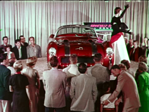 "vídeos y material grabado en eventos de stock de 1954 woman posing by pontiac bonneville special ""car of the future"" spinning on platform / audience - feria comercial"