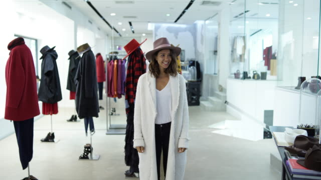woman posing in a clothing store - cappello video stock e b–roll